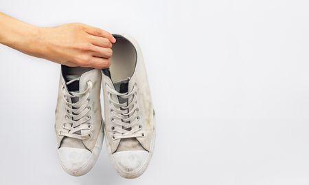 White dirty sneaker shoes with hand holding on white background
