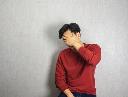 Gesicht von einer Hand bedeckt, und ein Mann mit rotem Shrit Standard-Bild