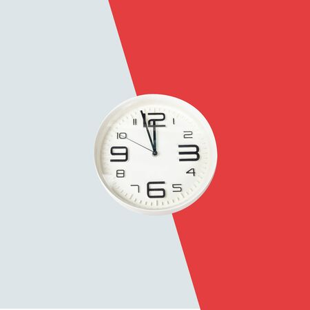 Clock showing time at 12 with red and grey background Stockfoto