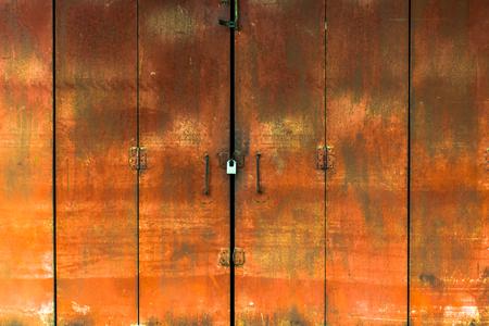 Red iron door with a padlock to lock. 免版税图像