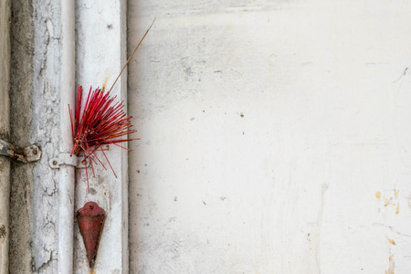 Incense sticks in red jar on a wall. Traditional Asian culture
