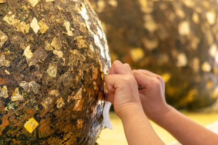 The girls hand hand put a Gold leaf on the stone ball background
