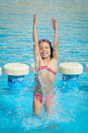Happy Young Girl Plays In A Pool Water  photo