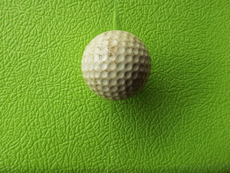 Golf ball past usage. On rough green background