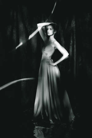Beautiful woman in evening dress on dark background stand on floor with a light blur from freezlight