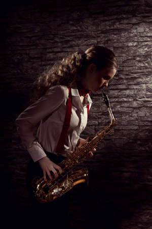 Beautiful girl with saxophone in mens dress