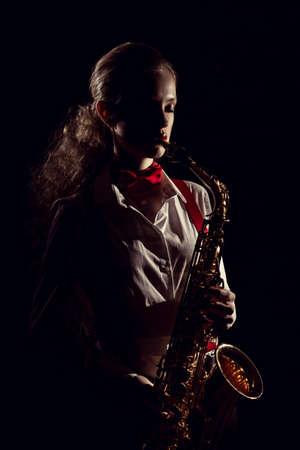 Beautiful girl with saxophone on dark stone wall