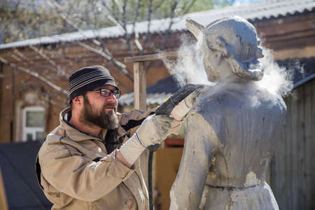 Renovator is engaged in the restoration of the statue Stock Photo
