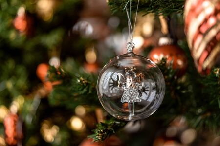 Christmas transparent ball hanging on pine branches with festive background