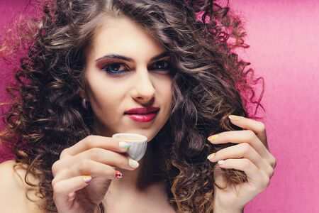 beautiful curly girl with colourful manicure drinking from a very small cup Stok Fotoğraf