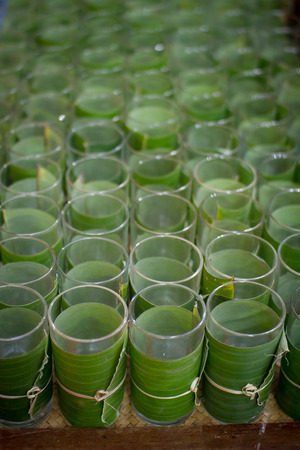 Glass of water wrapped with banana leaves photo