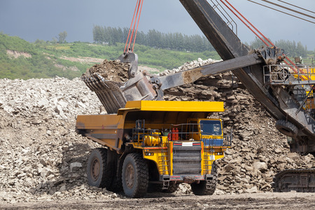 Loading the gold ore into heavy dump truck at the opencast mining photo