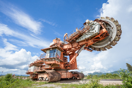 huge coal mining coal machine under cloudy and blue sky photo