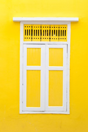 Vintage window on yellow cement wall photo