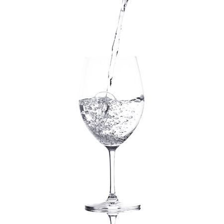 ewer: pure water is emptied into a glass of water Stock Photo