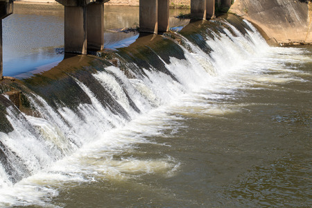 flowing water: Water over concrete dam for agriculture.