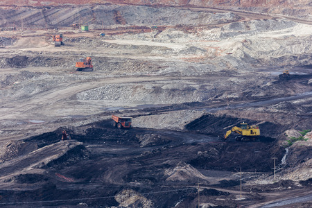 yellow backhoe work in coalmine.