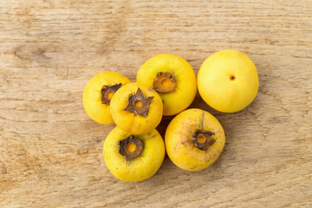 ebenaceae: Gold Apple, Diospyros decandra Lour. Thai fruit and Thai herb on  wooden table  background.