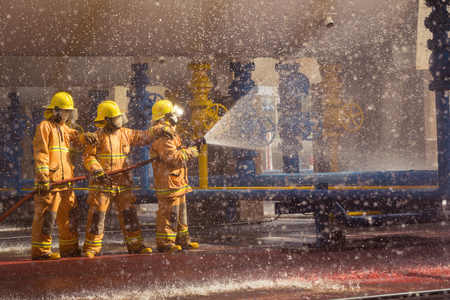 pyromania: Firefighters training, foreground is drop of water springer, Selective focus