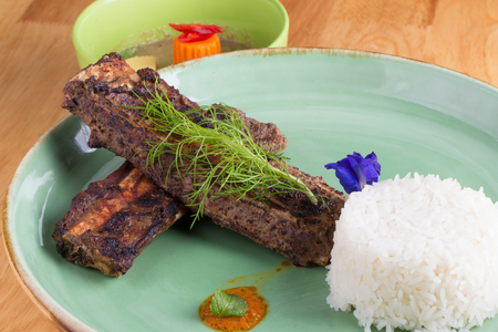 Grilled pork ribs and rice on plate