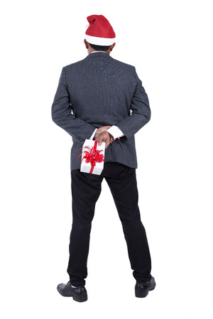 Portrait of a business man wearing a Santa Claus hat with holding up a small Christmas gift box on white background.