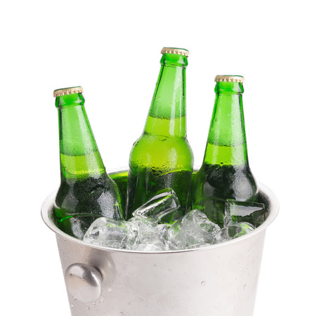 beer bucket: cold bottles of beer in bucket with ice on white background