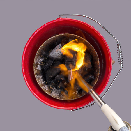 propane gas: Firing up charcoal briquettes for the BBQ grill. Starting a grill with propane gas torch. Stock Photo