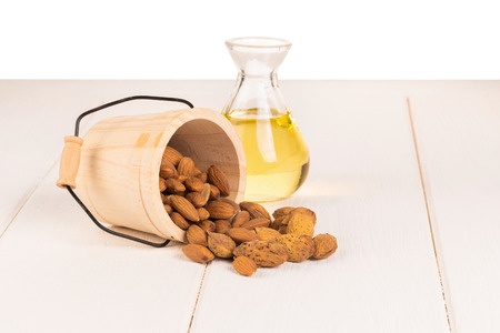 Bottle of almond oil and almonds on white wooden background