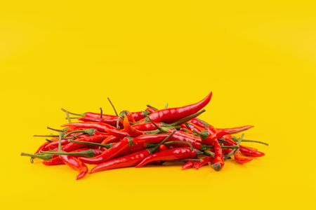 Red hot chili peppers isolated on yellow background. Stock Photo
