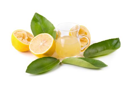glass bowl of freshly squeezed lemon juice, lemon squeezer and ripe lemons on white background.