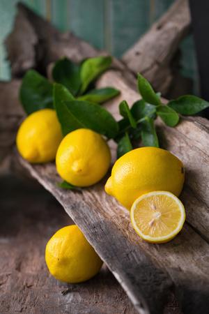 Fresh ripe lemons on Dark vintage wood texture background. Stock Photo