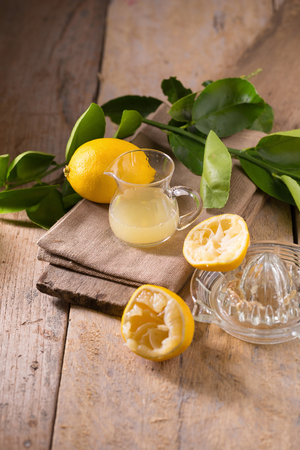 glass bowl of freshly squeezed lemon juice, lemon squeezer and ripe lemons on wooden background.