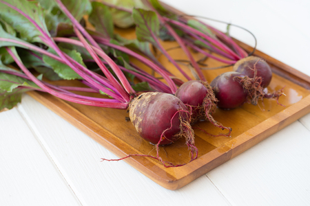 Fresh beetroots with leaves on white wooden table.