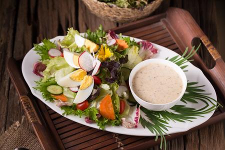 Shot of green salad with radish and hard-boiled egg on white plate with fork and napkin.