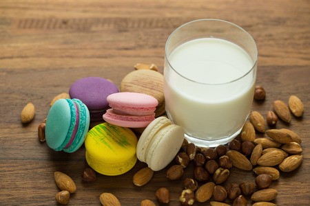 Tasty macaroons and cup of milk with almond on wooden background. Selective focus.