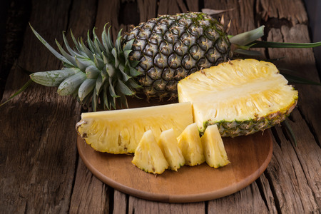 Ripe pineapple and pineapple slices on a wooden background tropical fruits.