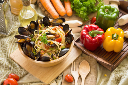 mussel and spaghetti on a deep wooden bowl. homemade food style.
