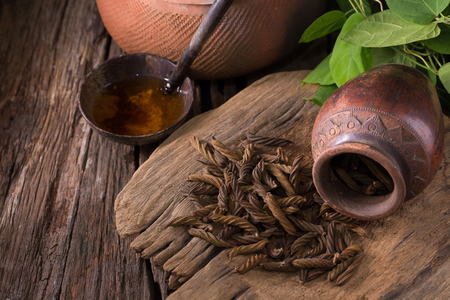 East Indian screw tree and Tea ,Thai herb for health on wooden background.