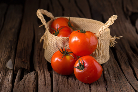 Tomato In the basket on a wooden background. Stock Photo