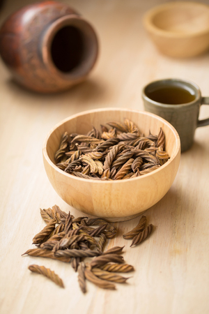 phlegm: East Indian screw tree and Tea ,Thai herb for health on wooden background.