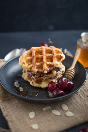 Honey on waffles with cherry berries on dark wooden background. breakfast concept.