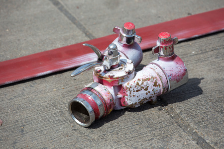 strapped: Rolled into a roll red fire hose, Fire equipment extinguishers ready to use in the outdoor.