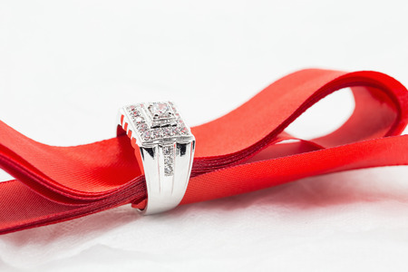 Diamond wedding rings in the Red ribbon on white. selective focus.