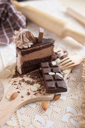 chocolaty: chocolate cake slice with chocolate cream and chocolate bar. cake background concept.