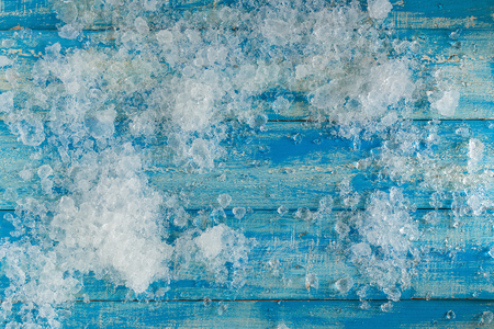 Crushed ice cubes on vintage blue wooden table. Top view. Stock Photo
