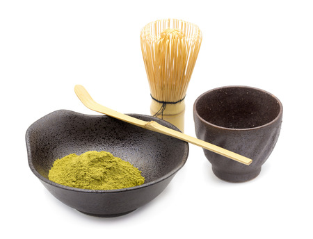 Set of Matcha green, matcha powder, wooden spoon and whisk isolated on white background.