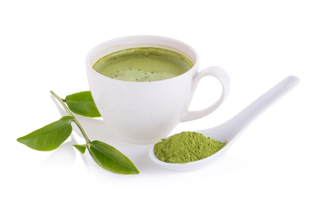 matcha powder in White ceramic spoon and Green tea matcha latte cup isolated on white background.