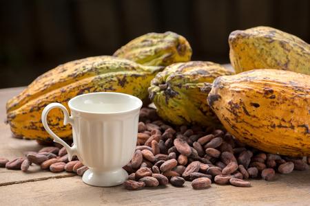 Ruwe cacaobonen en cacaopeul op een houten oppervlak. Stockfoto