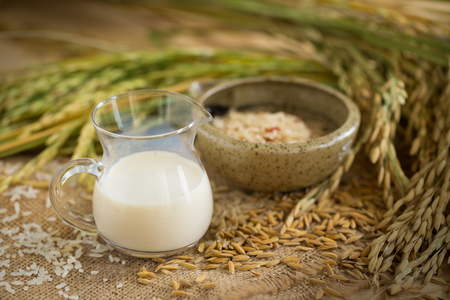 Rice milk and rice seeds on wooden table background.