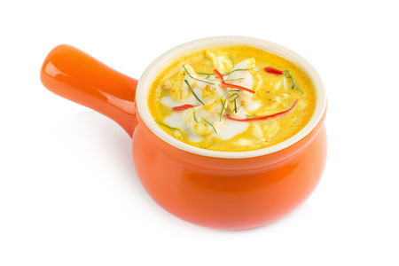 Curry crab, Seafood with Yellow curry sauce in orange ceramic pot, Isolated on white background. Stock Photo